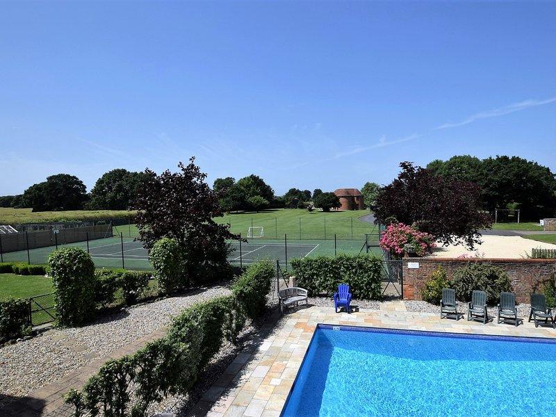 Vue du balcon sur la piscine et le court de tennis