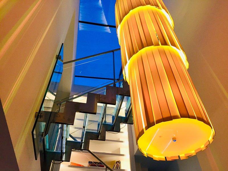 Escalera de cristal hecha a medida italiana junto a una estantería de 3 pisos