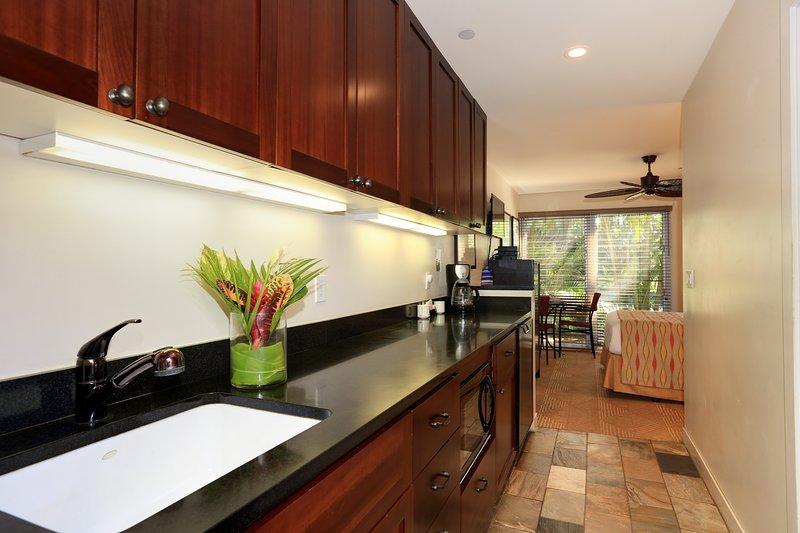Cocina de alta eficiencia con microondas, nevera pequeña y quemador de inducción.