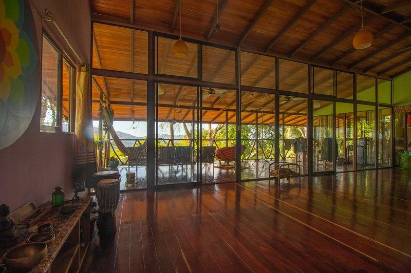 Área de estar de planta abierta con vistas al balcón a los bosques tropicales.
