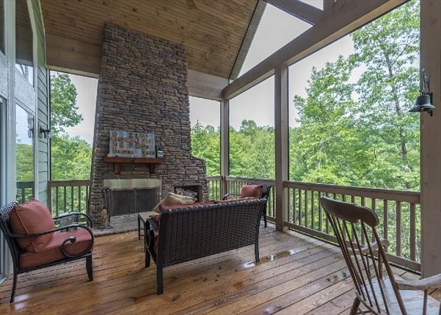 Grande véranda avec foyer au bois, plafond voûté et