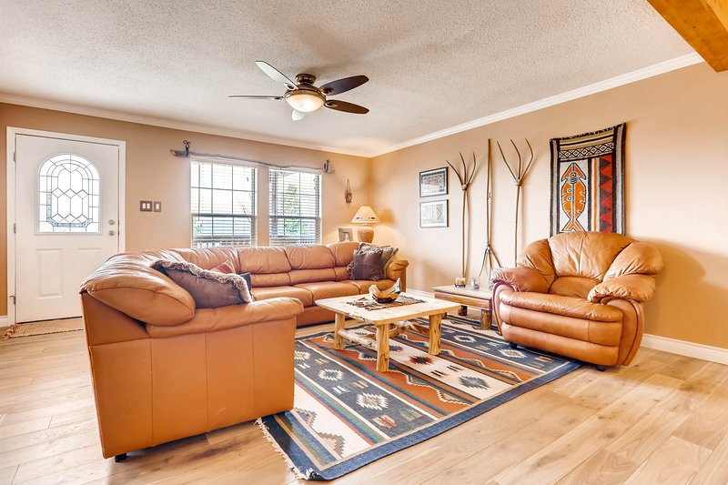 The family room has new comfortable leather seating and gorgeous hard wood flooring.