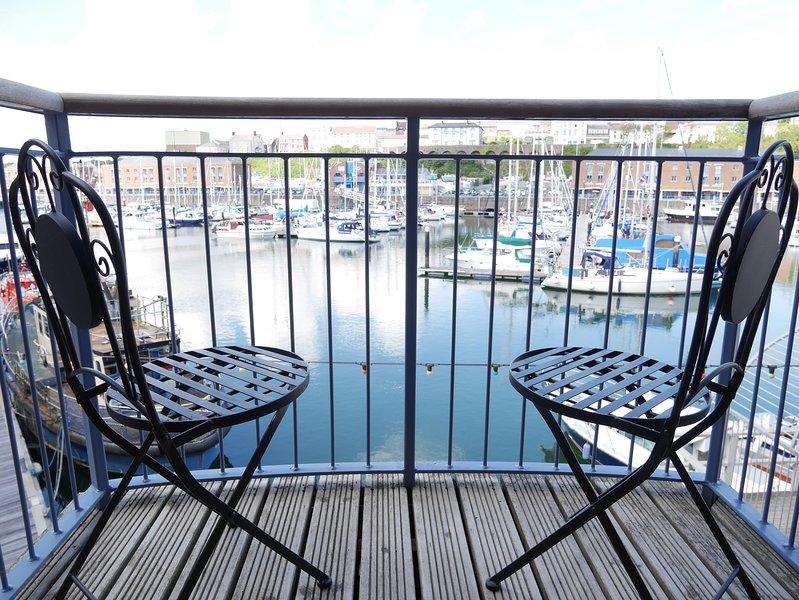 Balcone con posti a sedere per 2, con vista sul porto turistico di Milford.