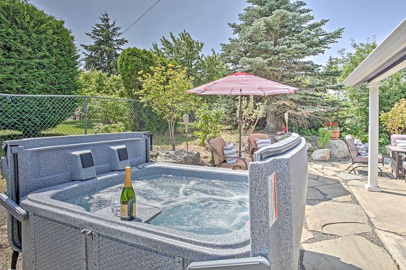 Toast à vos vacances tout en vous relaxant dans le bain à remous sur le patio de dalles.