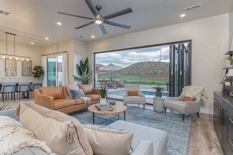 Living area with views of outdoor pool and 8th Hole of Coral Canyon golf course