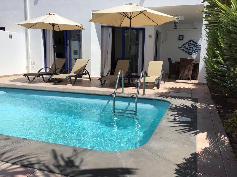 Jardín trasero privado, con piscina climatizada, con 3 puertas que dan a la piscina y área de comedor al aire libre