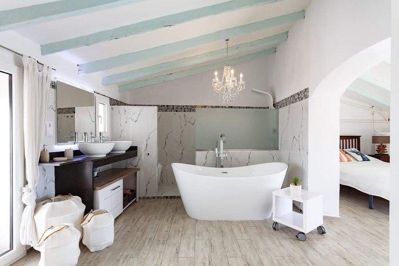 Ensuite badkamer, met groot bed en dakterras.