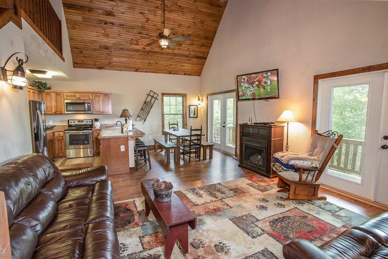 Open Concept Great Room, cozinha, sala de jantar com piso de madeira, tectos abobadados, lareira, TV HD Smart
