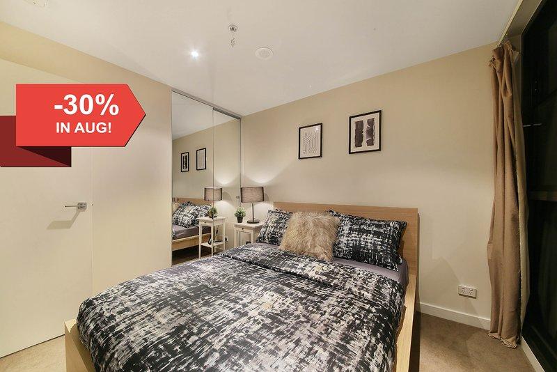 El dormitorio principal con una cama queen size y amp; almohadas de felpa.