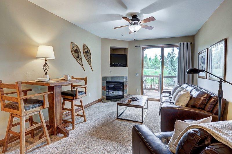 Acogedora sala de estar con chimenea de gas y TV de pantalla plana.