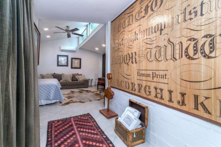 Sala de frente com cama queen size, sofá, área de estar e acesso privado ao deck, onde você terá uma bela vista!