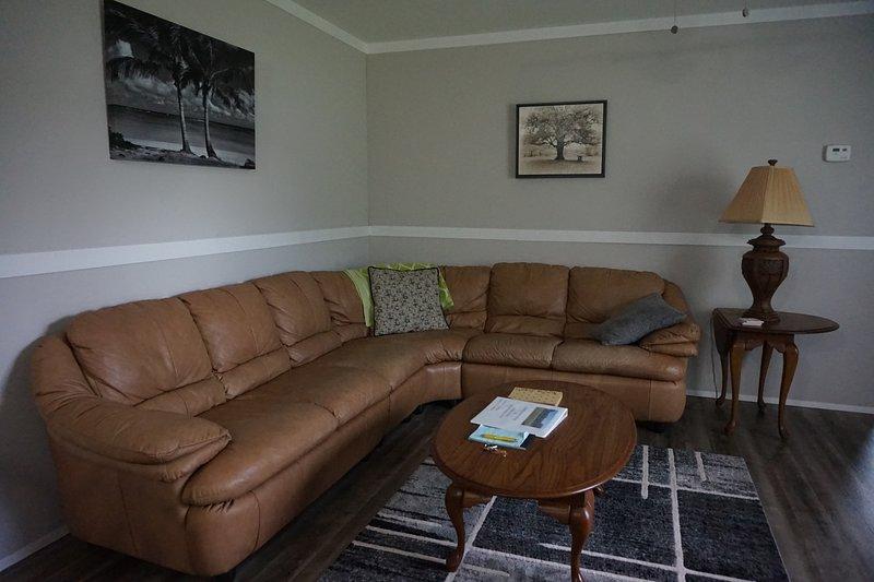 """Lussuoso divano componibile in pelle nel soggiorno con ventilatore a soffitto e smart TV da 55 """"."""