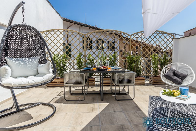 Exklusiv terrass med bord och 4 stolar och hängkomfortstol perfekt för frukostar och aperitiffer
