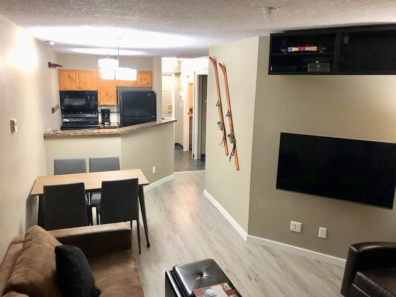 Living area with new Samsung 50' QLED 4K TV, new furnishings, new floors!