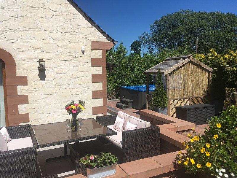 El encantador patio al aire libre con cómodos muebles de jardín y la bañera de hidromasaje en la parte trasera.