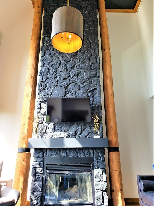 Living Area with a Beautiful Stone Fireplace and Flat Screen TV