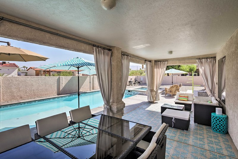 The enclosed yard boasts a spa, patio seating and mountain views.