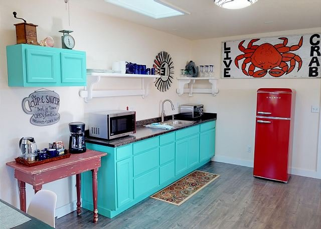 Colorful kitchenette includes microwave, toaster oven & fridge.