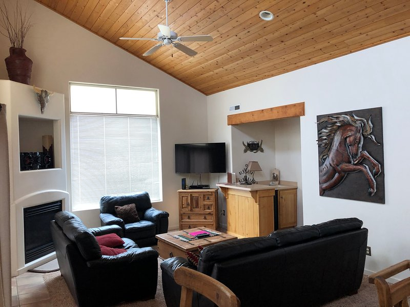 Family room with paneled wood ceilings and more great western art