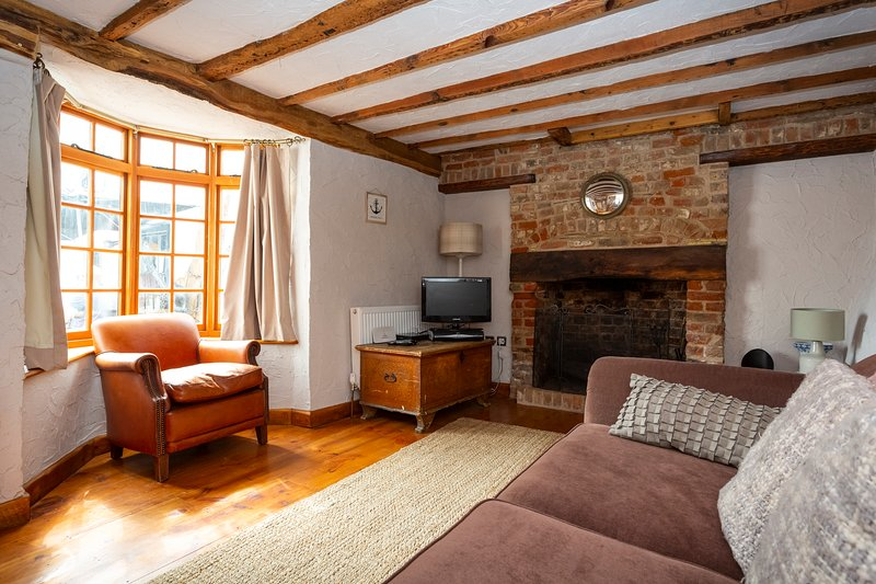 Beautiful lounge with wooden beams, wooden floor and open fire,