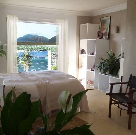 Camera da letto principale con bagno privato e porte sul ponte con vista.