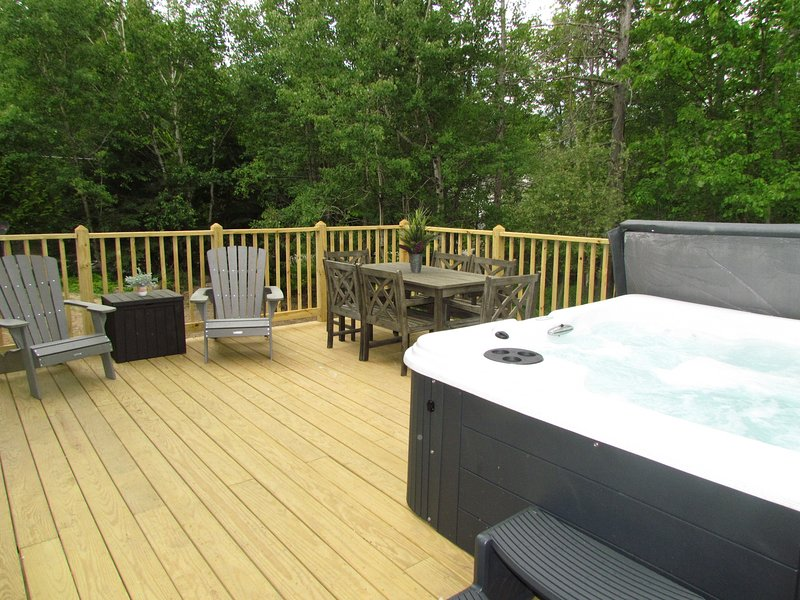 Large deck with 6 person table,  Adirondack chairs, and a 6 person hot tub to relax in!