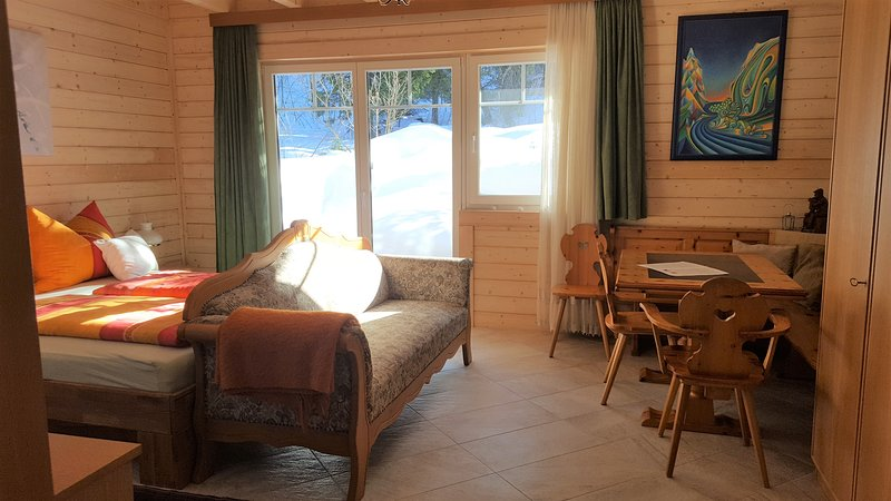 Large double bedroom with seating and views of the forest