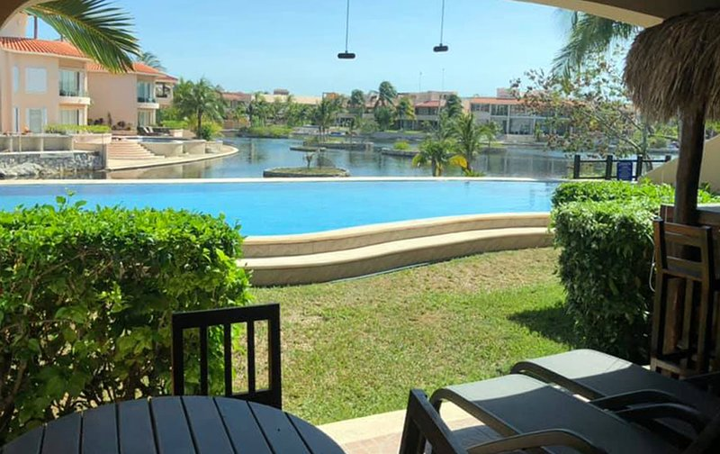 Sparkling turquoise pool overlooking salt water lagoon. Enjoy this view from your private terrace!