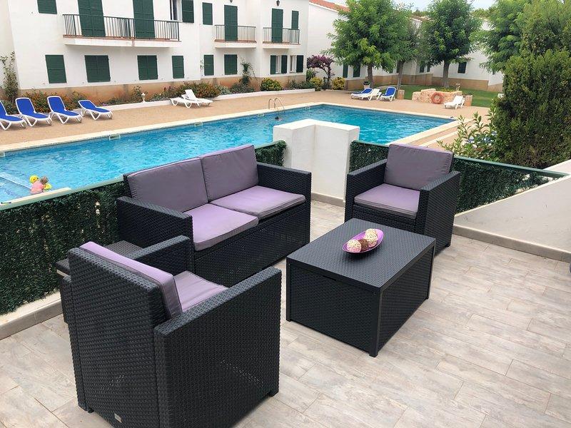 Terrazza area relax con piscina in background