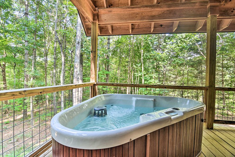 Sink into your private hot tub and enjoy the natural surroundings.