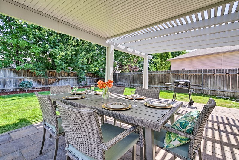 The patio and lush backyard features outdoor seating and a gas grill.