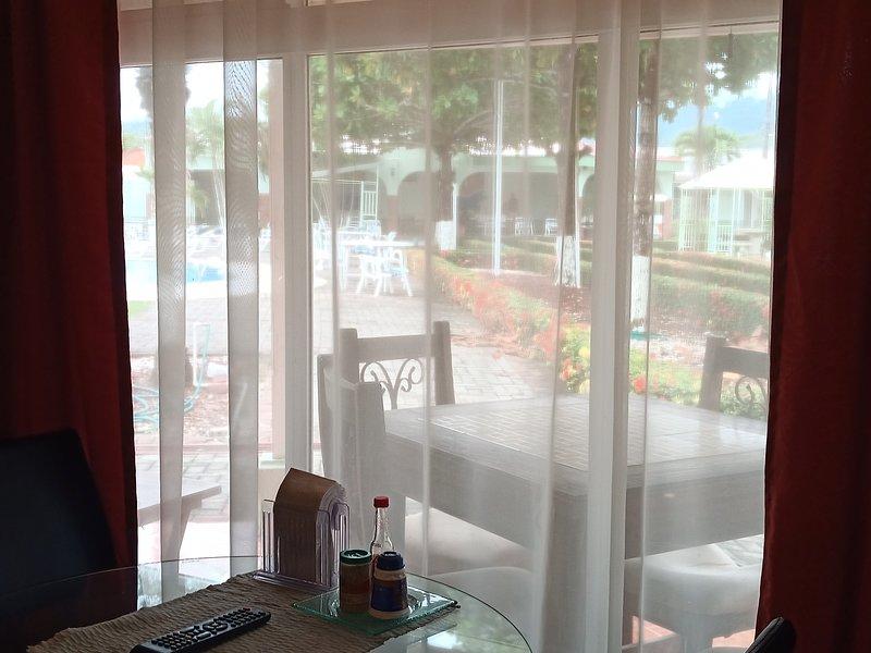 Vista all'esterno dal tavolo della cucina. Patio, piscine, montagne.