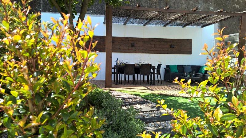 Garten mit Sonneneinstrahlung und Terrasse mit Ess- und Sitzbereich