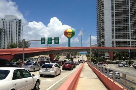 The famous Hallandale Beach Boulevard that leads to the beach. Behind the globe is the sea.