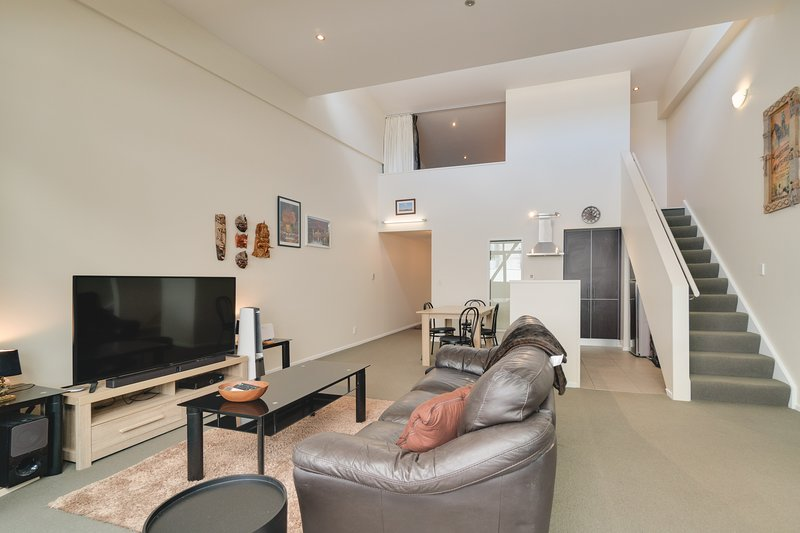 A great open planned living area with a comfortable couch and large TV.