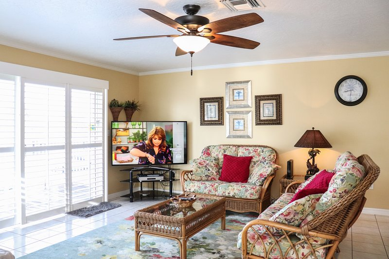 Sofas with outdoor views and smart HDTV in bright, sunny lounge area