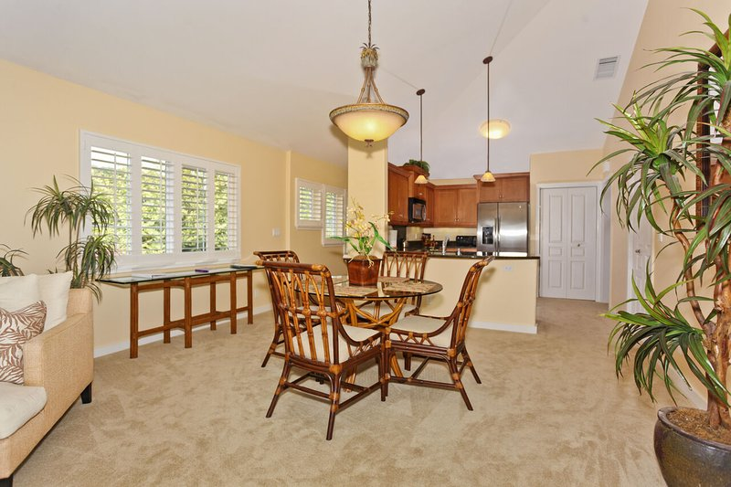 Dining area with table, chairs, many potted plants, and view of the kitchen in the background.
