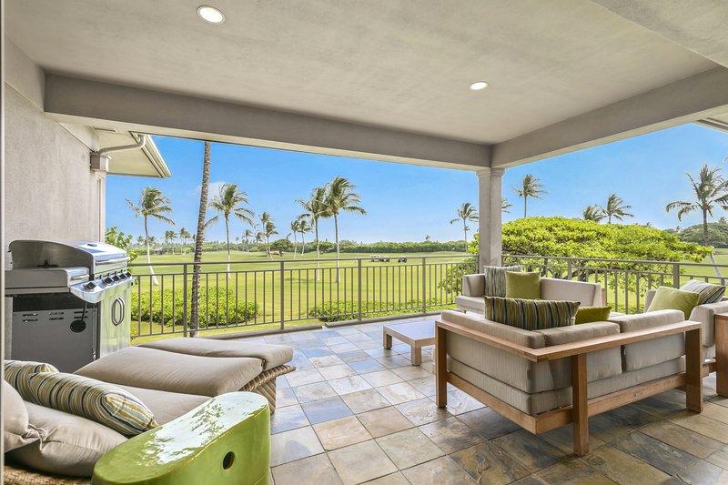 Generoso Lanai cubierto con amplios asientos y vistas del campo de golf Hualalai Green, palmeras y el Océano Pacífico más allá.
