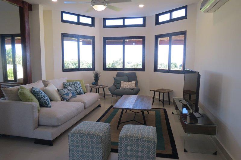 Elegante sala de estar decorada profesionalmente con vista al patio trasero y al océano Pacífico