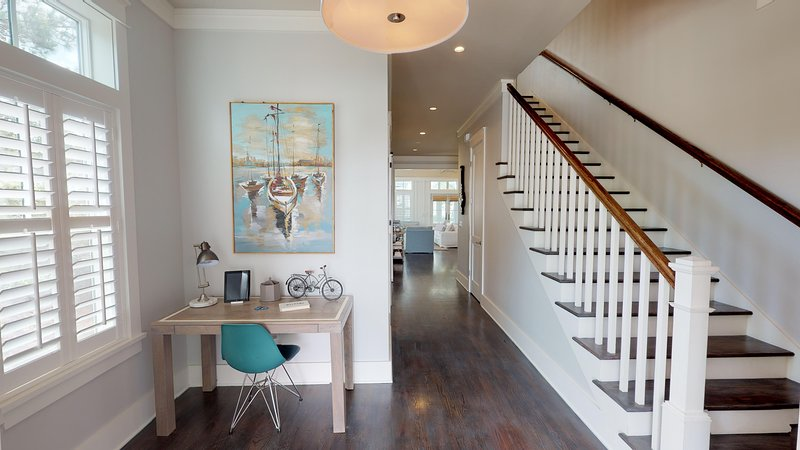 Bright entryway with tall ceilings and inviting warm colors welcome you into this beautiful beach home; powder room in the main hallway