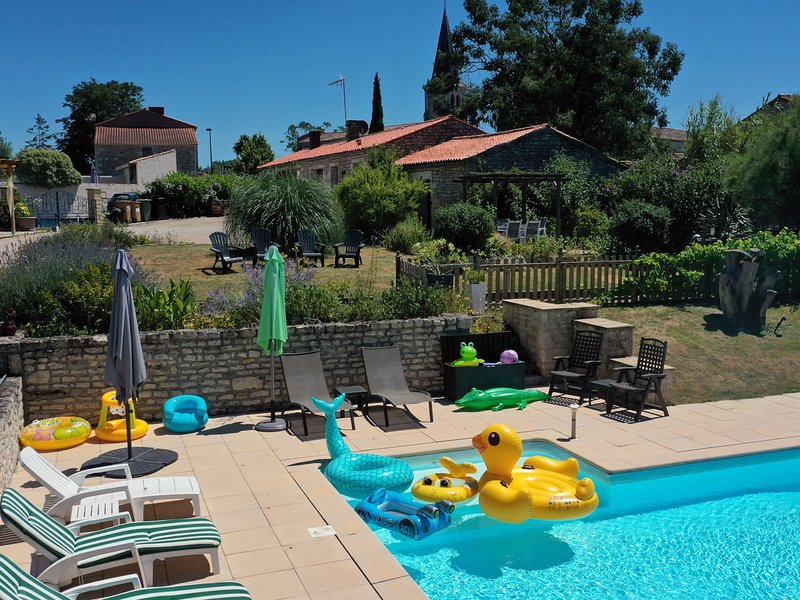 Relax by the heated pool at L'Ecurie Holiday Cottage