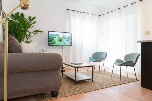 The living room area has all new furnishing including a new flat screen TV  and a sofa.