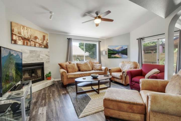 Cozy living room with couch, 2 chairs, flat screen TV and wood burning fireplace!