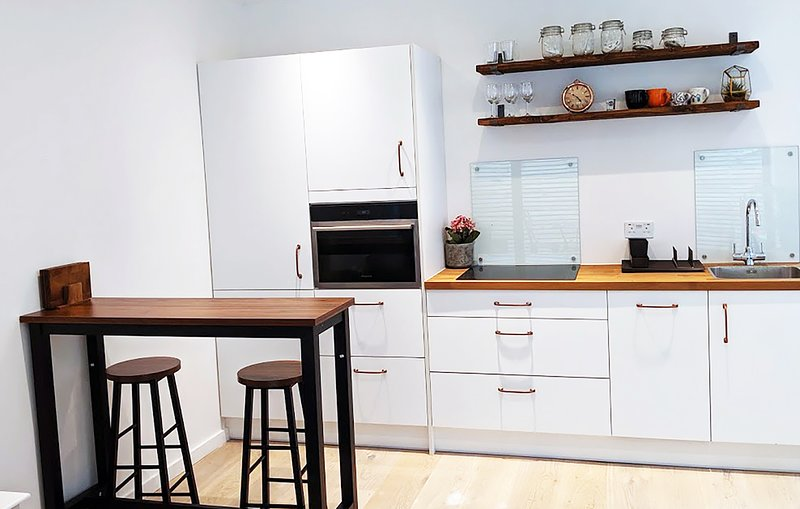 Modern open plan kitchen with an induction hob, a combi oven and an integrated dishwasher