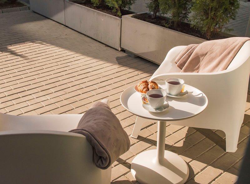 Terrazza privata con sedie, tavolo, coperte calde, focacce e tè per godersi il bel tempo