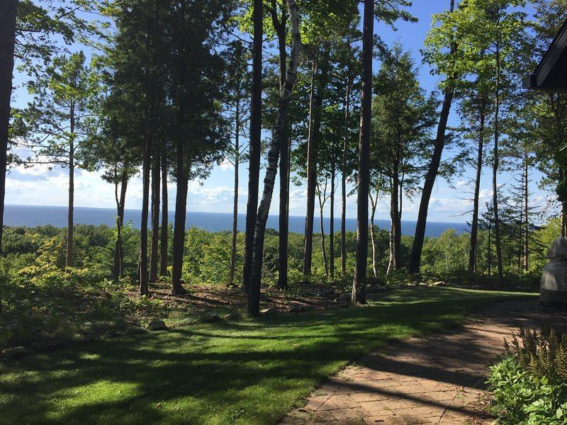 Enjoy water and wooded views as you walk to the front door.