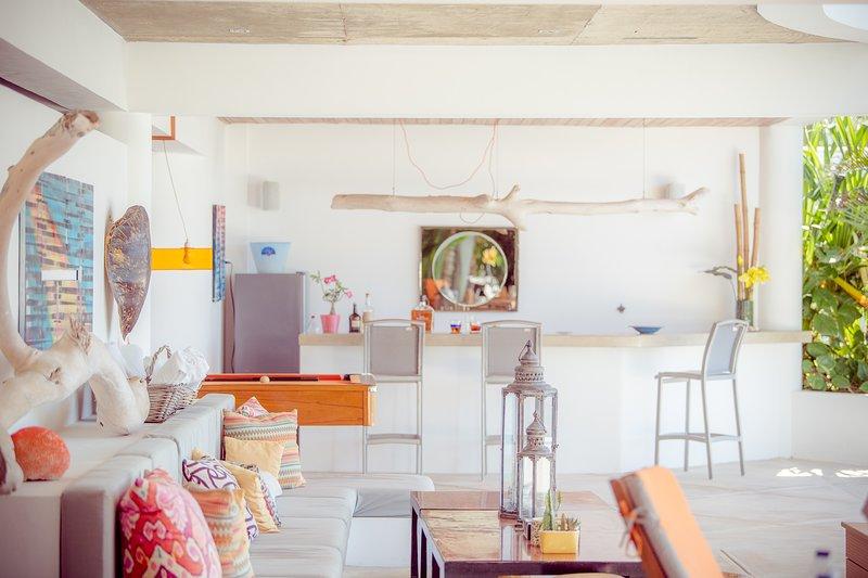 Área de descanso junto a la piscina: bar, mesa de billar, jacuzzi, sofás, sillones