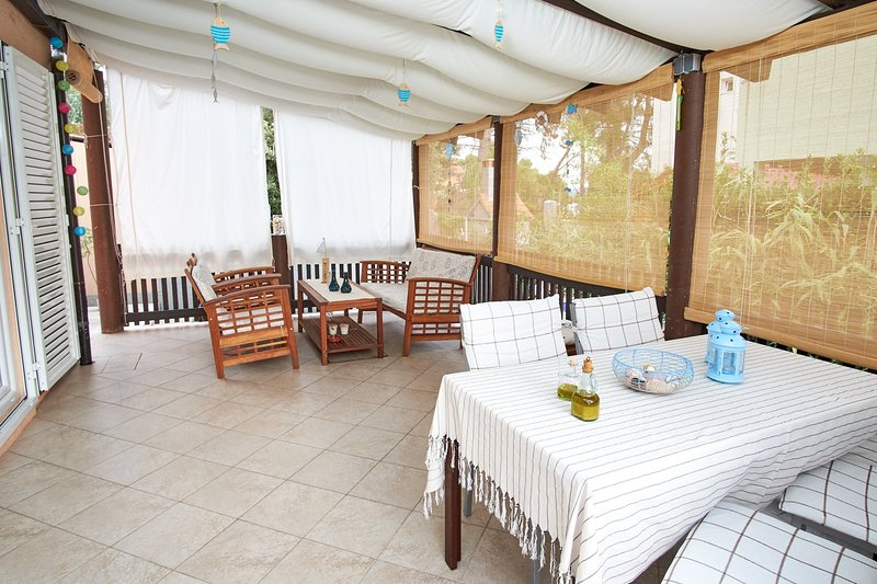 Main covered terrace with dinning and tea tables. Serves as a living room / hanging around place