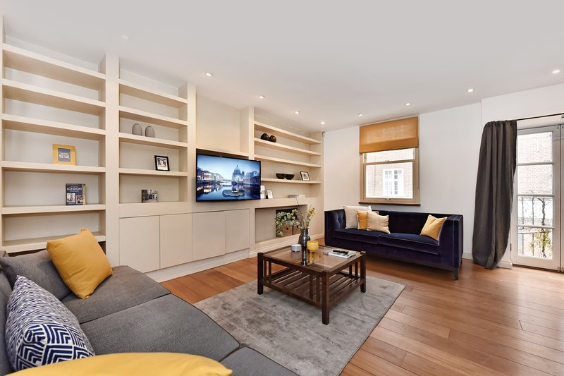 The bright and elegant living room with lounge, dining table for 6 and well-equipped kitchen