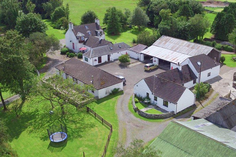 Vista aérea del patio, casa de campo y parque de juegos para los niños.
